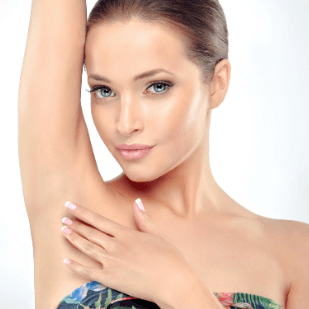 Dark haired woman standing with her right arm over her head showing her underarm laser hair removal