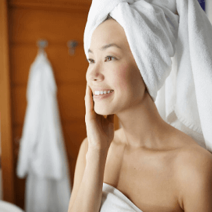 Asian female with white towel wrapping her head and hair, touching her face with right hand