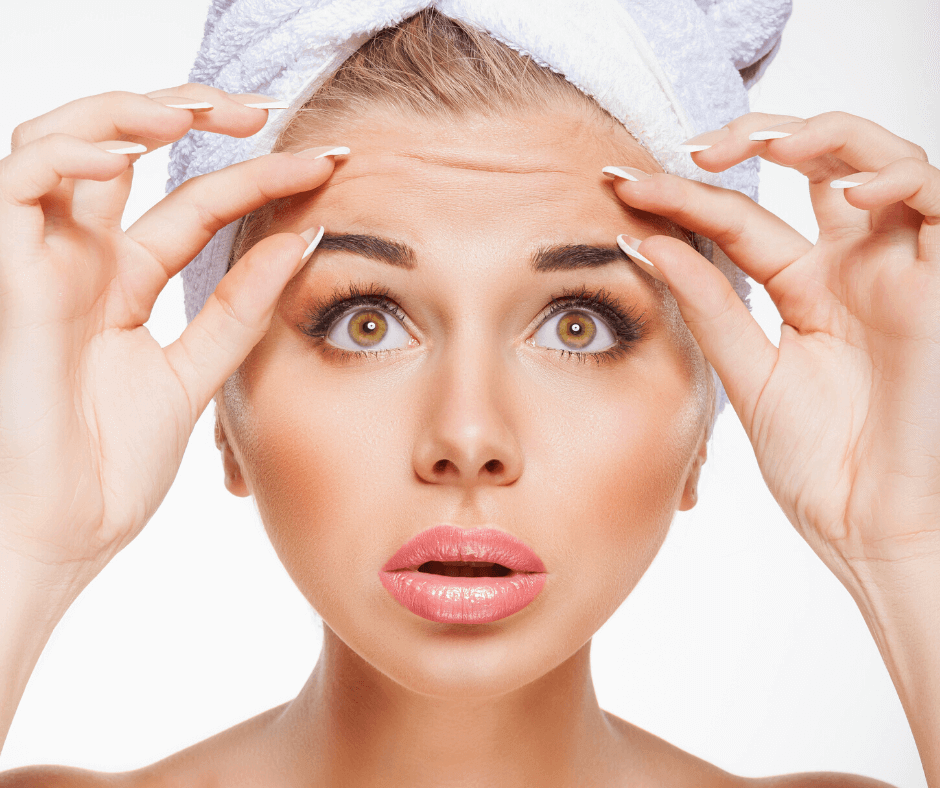 Blonde hair woman with brown eyes and glowing facial complexion with a towel wrapping hair pinching her eyebrows.